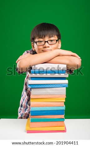 Schoolboy leaning on the stack of books - stock photo