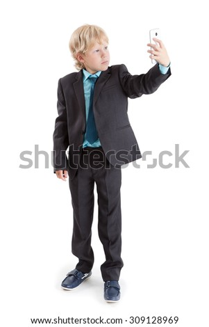 Schoolboy looking at screen of mobile phone while making selfie, full-length isolated on white background - stock photo
