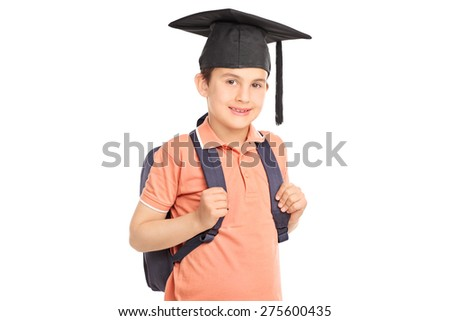 Schoolboy looking at the camera, carrying a backpack and wearing a graduation hat isolated on white background - stock photo