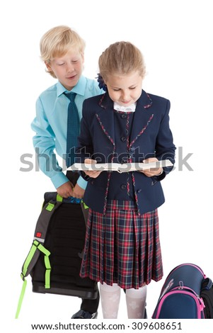 Schoolboy looking from the back of schoolgirl in opened book in girl`s hands, isolated on white background - stock photo