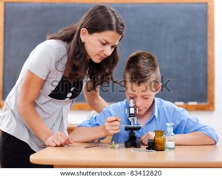Schoolboy looking inot microscope while the biology teacher is attending him - stock photo