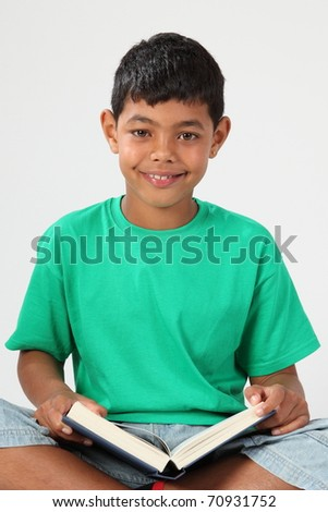 Schoolboy looks up from reading with happy smile - stock photo