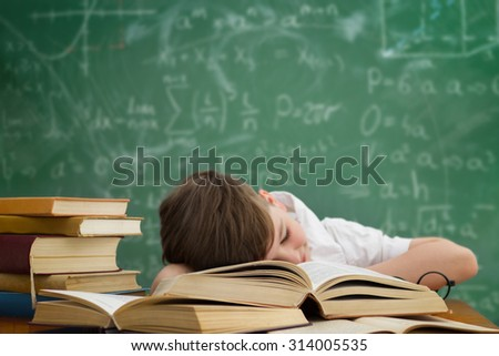 schoolboy lying on book and sleeping in class during lesson - stock photo