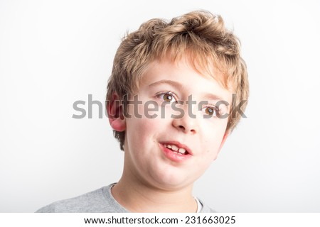 Schoolboy making funny faces - stock photo