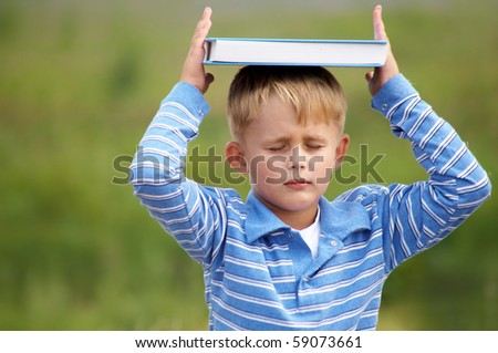 schoolboy meditates on the head with  book on the background of green meadows - stock photo