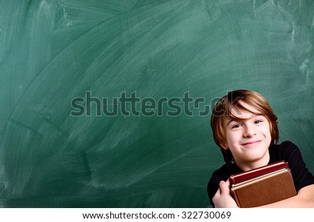 schoolboy over empty school green chalkboard