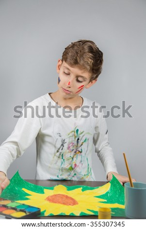 Schoolboy painting - stock photo