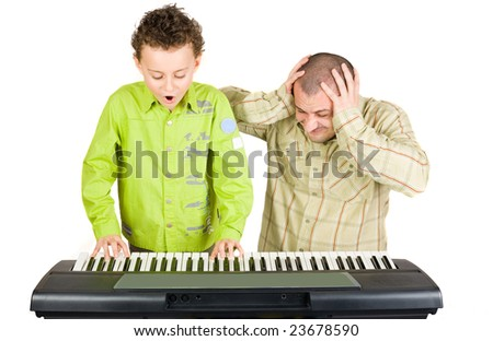 Schoolboy playing badly at the piano while the teacher shows disappointment - stock photo
