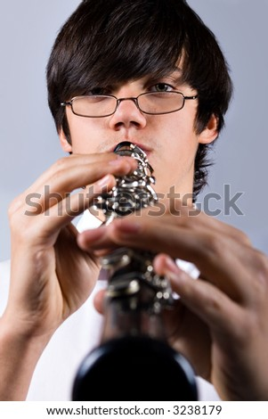 Schoolboy playing the clarinet, people diversity series - stock photo