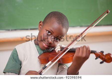 Schoolboy playing the violin in a classroom - stock photo