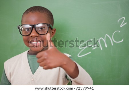Schoolboy posing with the the mass-energy equivalence formula and the thumb up in front of a blackboard - stock photo