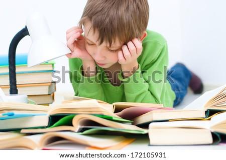 schoolboy reading book lying down on floor - stock photo