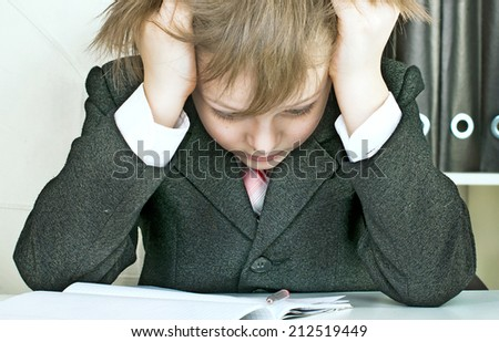 schoolboy reads the textbook sitting at the table - stock photo