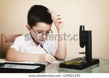Schoolboy records the results of the analysis - stock photo