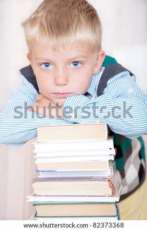 schoolboy relies on a big pile of books, portrait - stock photo