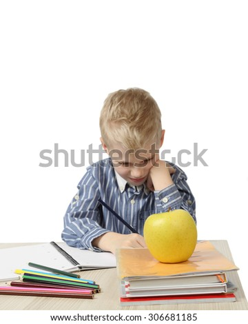 Schoolboy sits near the desk with school supplies and big apple on foreground isolated on white background with focus on apple - learning and homework - stock photo