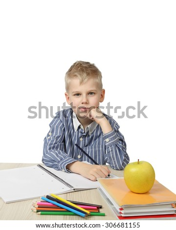 Schoolboy sits thoughtful with chin rested on fist near the desk with school supplies and big apple on foreground isolated on white background - ponders lesson - learning and homework - stock photo