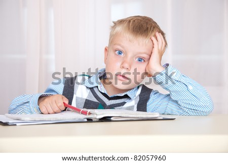 schoolboy sitting at a desk with a notebook - stock photo