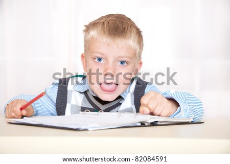 schoolboy sitting at a desk with a notebook and pencil, and shows tongue - stock photo