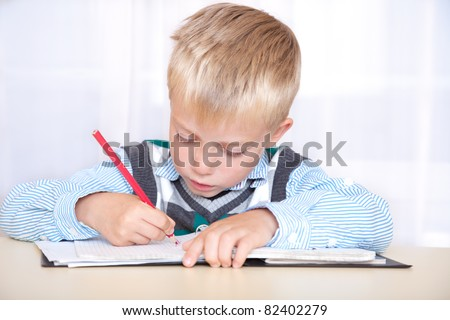 schoolboy sitting at a desk with a notebook and pencil and write. portrait, close up - stock photo