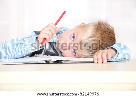 schoolboy sitting at a desk with a notebook and pencil. portrait, close up - stock photo