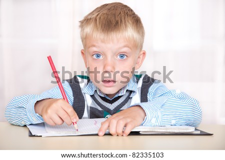 schoolboy sitting at a desk with a notebook and thinking how to do the job. - stock photo