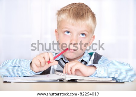 schoolboy sitting at a desk with a notebook and thinking how to do the job. boy with a thoughtful face - stock photo