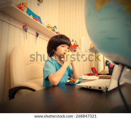schoolboy sitting at a table with a laptop and eating apple. instagram image retro style - stock photo