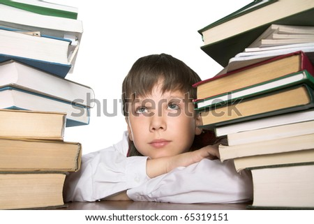 Schoolboy sitting at the table pilled up with books - stock photo