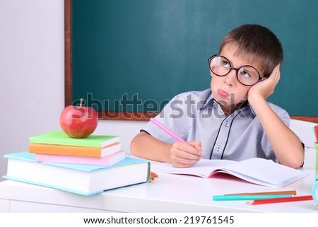 Schoolboy sitting in classroom on blackboard background - stock photo