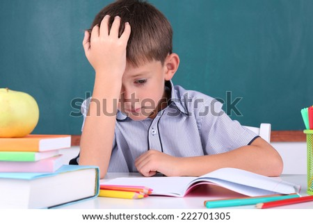 Schoolboy sitting in classroom on blackboard background - stock photo