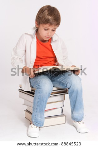 Schoolboy sitting on a pile of books reading a big one - stock photo