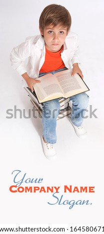 Schoolboy sitting, on a pile of books reading one, aerial view - stock photo