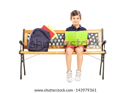 Schoolboy sitting on a wooden bench and reading a book isolated on white background - stock photo
