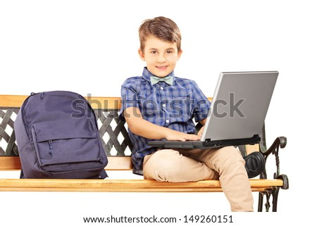 Schoolboy sitting on a wooden bench with school bag next to him and working on a laptop isolated on white background