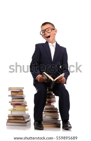 Schoolboy sitting on the huge stack of books  isolated over white background