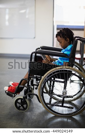 Schoolboy sitting on wheelchair and using digital tablet at school