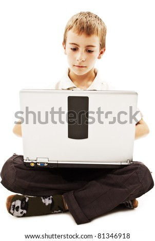 Schoolboy sitting with legs crossed on floor and using notebook - stock photo