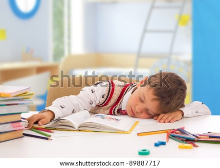 schoolboy sleeping on the table with notebook - stock photo