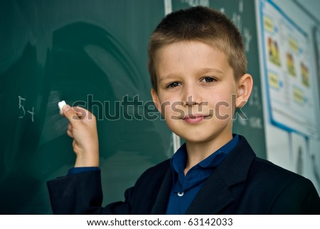 Schoolboy standing at the blackboard