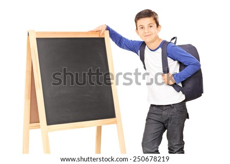 Schoolboy standing by a blackboard and carrying a backpack isolated on white background - stock photo