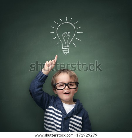 Schoolboy standing in front of a blackboard with a bright idea light bulb above his head concept for innovation, imagination and inspirational ideas - stock photo