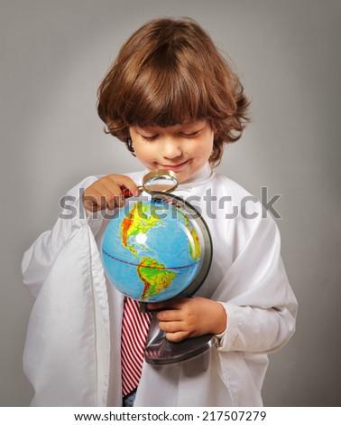 schoolboy studying Globe - stock photo