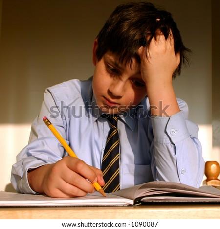 Schoolboy studying in his bedroom - stock photo