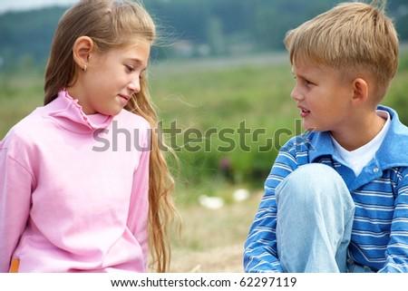 schoolboy talking to a schoolgirl outdoors - stock photo