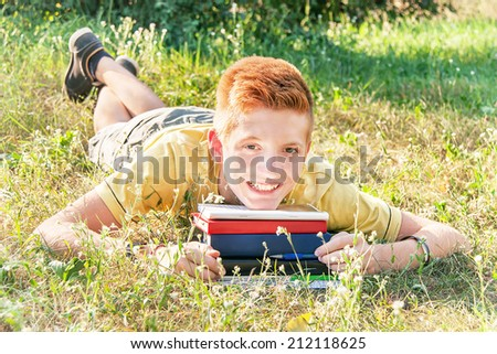 Schoolboy teen (teenager) with books is lying in the city park. Young smiling red-head boy studying on the grass. Caucasian cute male model (14 year). Sunny day. Education concept. Close up, outdoors. - stock photo