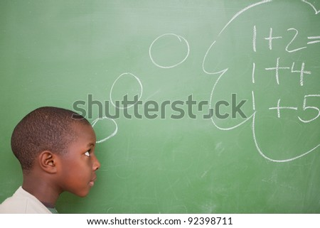 Schoolboy thinking about additions in front of a blackboard - stock photo