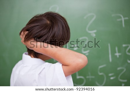Schoolboy thinking while scratching the back of his head in front of a chalkboard - stock photo