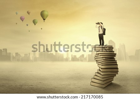 Schoolboy using binoculars for looking air balloon on the sky - stock photo