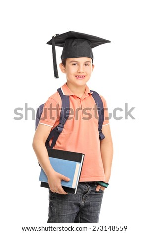 Schoolboy with a graduation hat carrying a backpack and holding a couple of books isolated on white background - stock photo